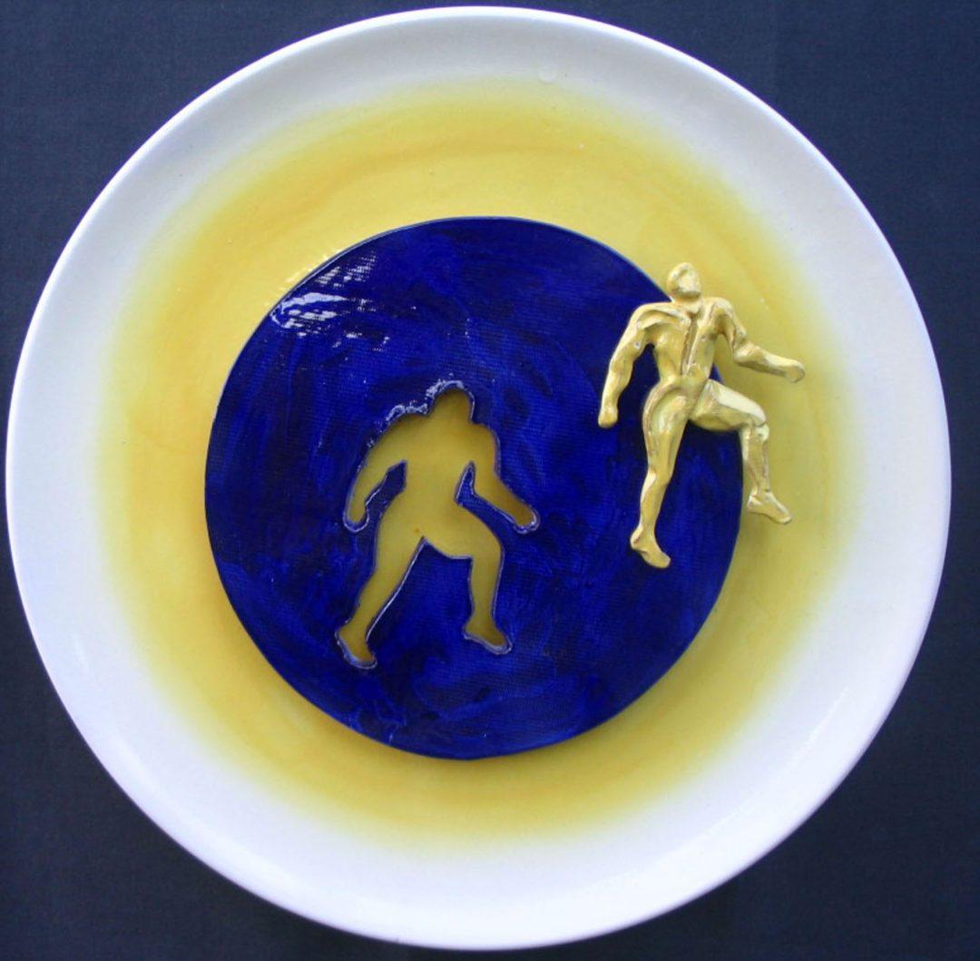 Figura gialla su disco blù
